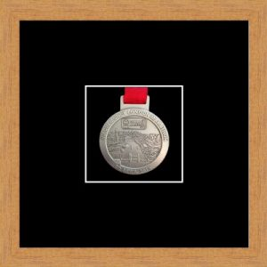 Light woodgrain picture frame for one marathon medal with black mount